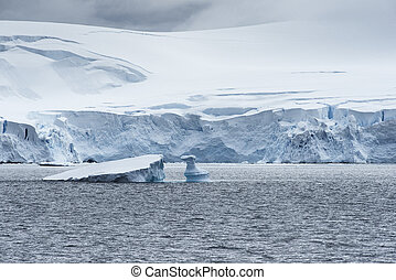 Low clouds over the snow capped mountains and chunks of ice floating at Admiralty Bay, King George Island, Antarctica