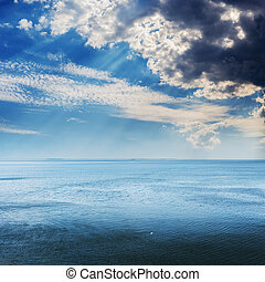low dark stormy clouds over blue sea