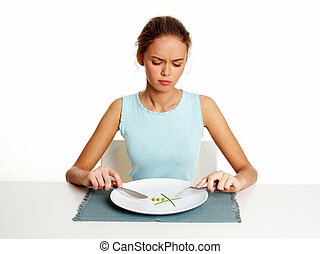 Low diet - Unhappy young woman dieting with peas and leeks,...