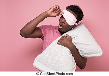 Low energy tired adult african man looiing aside peeping through sleeping mask