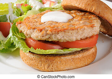 Closeup of a low fat healthy chicken or turkey burger with a salad