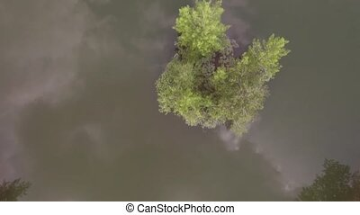 Aerial view. Low flight over lake at sunny summer morning. Green trees and hills, reflection of clouds on the lake surface.