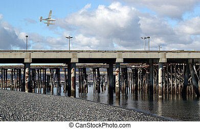 Low flying sea plane over the commercial shipping dock