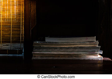 Low key image of stack of books setting on wooden table with sunlight through curtain in the background. (Selective focus)