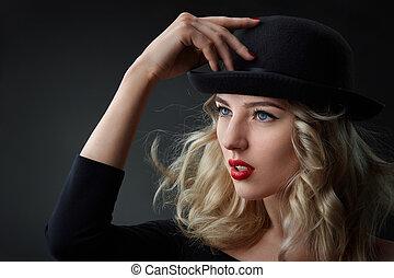 Low key portrait of glamour blond woman, wearing a hat, ...