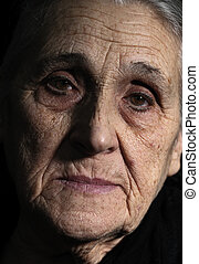 low key portrait of old woman close- up