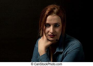Low key portrait of pensive young woman