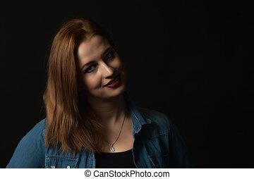 Low key portrait of smiling young woman