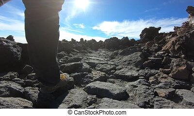 Low level footage of hiking a path across volcanic...