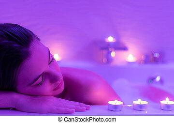 Low light face shot of woman in foam bath.