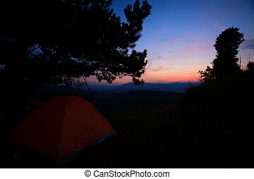 low light sunset over the red tent in high mountain