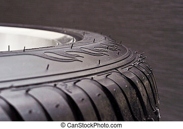 low-profile car wheel on a black background close up