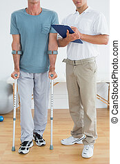 Low section of a therapist and disabled patient with reports