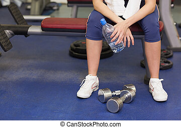 Low section of a tired and thoughtful woman in gym - Low...