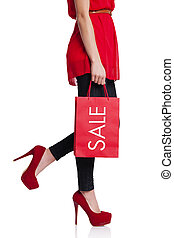 Low section of a woman with her red shopping bag