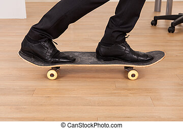 Low section of businessman on skateboard