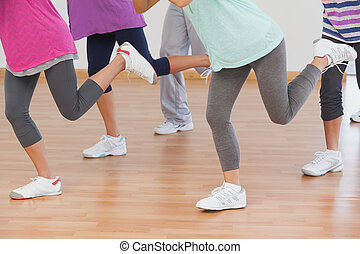 Low section of class and instructor doing pilates exercise