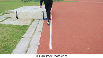 Low section of female athlete measuring high jump field with footstep. She is walking on a sports track 4k