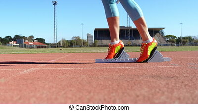 Low section of female athlete taking starting position on a ...
