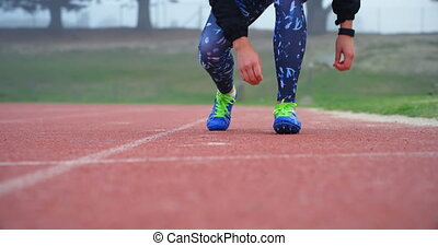 Low section of female athlete tying shoelace on a running track at sports venue. She is walking on a running track 4k