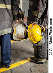 Low Section Of Firemen Holding Helmets