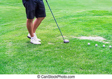 Low section of golf player ready to hit the ball
