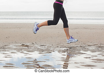 Low section of healthy woman jogging