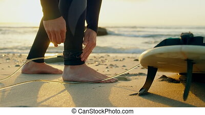 Low section of mid-adult caucasian male surfer tying ...
