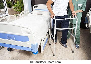 Low Section Of Nurse Helping Patient In Using Walker