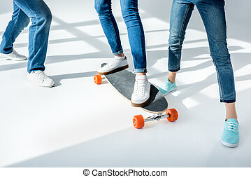 Low section of parents standing near daughter riding skateboard