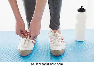 Low section of woman tying shoes with water bottle on floor