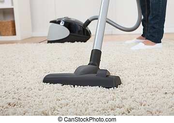 Low Section Of Woman Vacuuming Floor