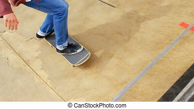 Low section of young man doing skateboard trick on skateboard ramp at skateboard court 4k