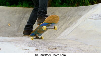 Low section of young man doing skateboarding trick on ramp in skateboard park 4k