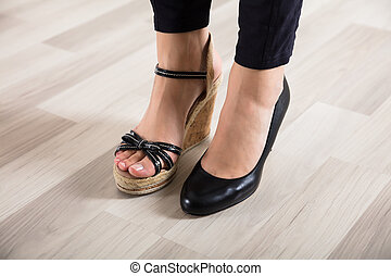 Woman's Feet With Two Different Footwear - Low Section View...