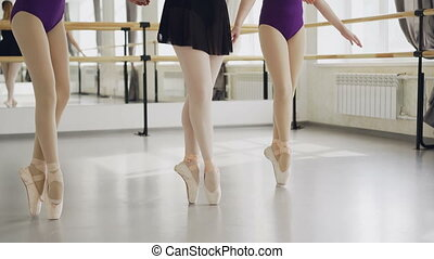 Low shot of female legs in ballet shoes doing plie then...