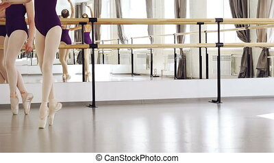 Low shot of girls' legs in ballet shoes walking on tiptoes making steps on floor of light studio. Choreography, classical ballet, art and children concept.