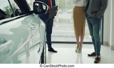 Low shot of prosperous people young couple buying new car in...