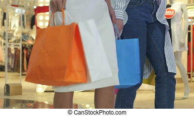 Low shot of two girls that are walking through a clothing store in colorful garments