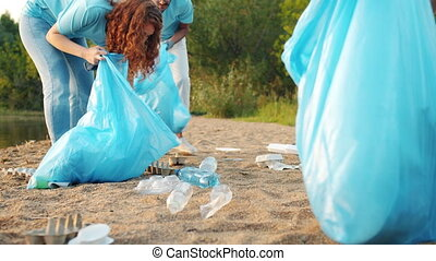 Low shot of youth volunteers gathering trash on the lake shore picking up garbage
