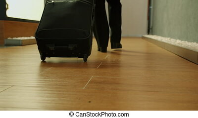 Low shot slow motion of female legs walking in hotel lobby with luggage while businesswoman travelling alone. Accommodation and tourism concept.
