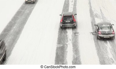 Low speed city road traffic passes by under snowfall