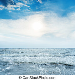 low sun in sunset over blue sea with waves