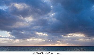 low sun through the clouds, dark ocean