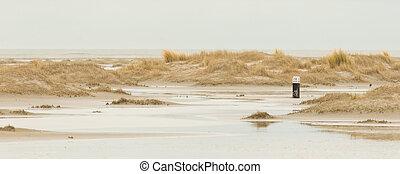 Low tide at the dunes of Ameland, dark sky, Holland