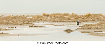 Low tide at the dunes of Ameland, dark sky, Holland