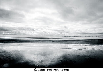 Black and white photograph of low tide beach