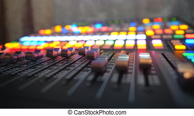 Low view of dj remote with moving buttons. Working process on recording studio. Amplifier and balance of sound. Musical player at party in night club. Brightly glow keys at background. Dolly shot