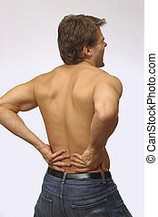 Lower back pain - Topless man with back pain presses on...