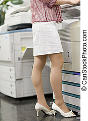 lower body of woman standing in front of photocopier